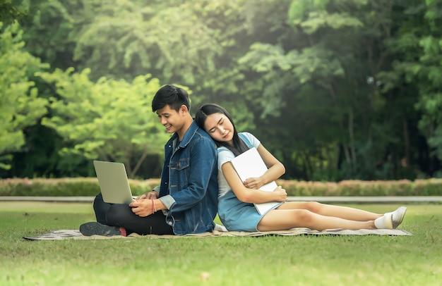 Portret szczęśliwi młodzi ucznie siedzi na parku i używa laptop outdoors