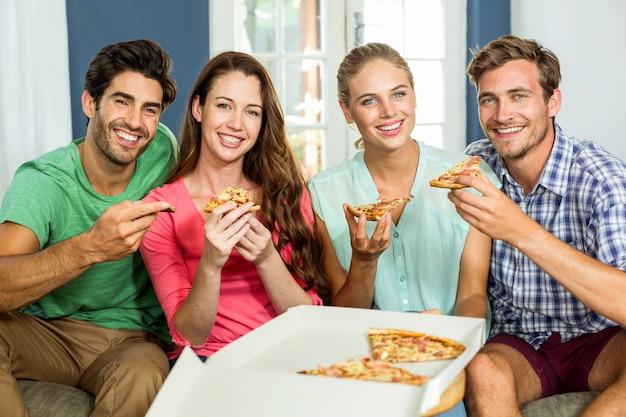 Portret szczęśliwi przyjaciele je pizzę