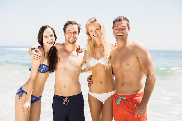 Portret szczęśliwi przyjaciele stoi wpólnie na plaży