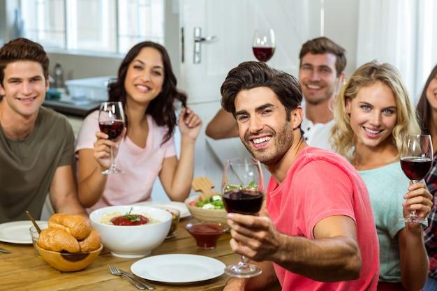 Portret szczęśliwi przyjaciele trzyma win szkła przy stołem
