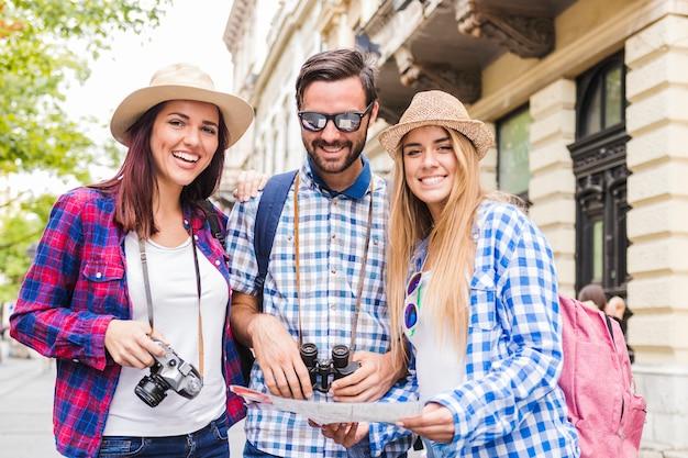 Portret szczęśliwi przyjaciele z mapą przy outdoors