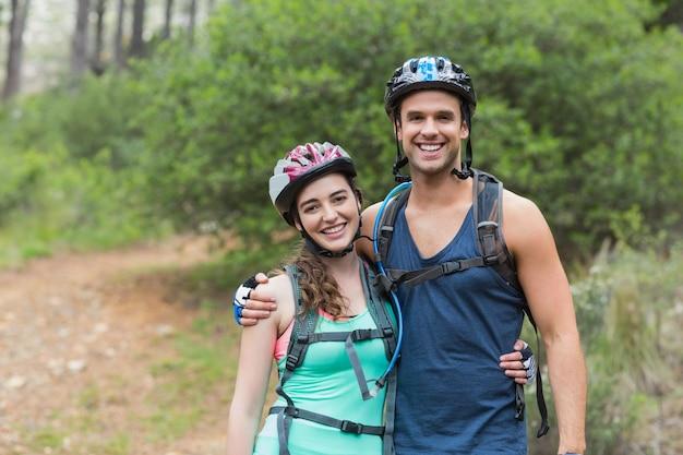 Portret szczęśliwi rowerzyści stoi w lesie
