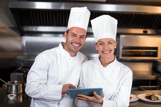 Portret szczęśliwi szefowie kuchni trzyma schowek w kuchni