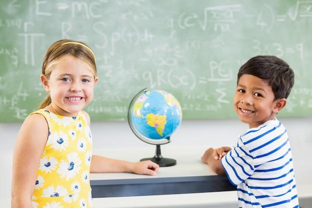 Portret szczęśliwi szkolni dzieciaki stoi w sala lekcyjnej