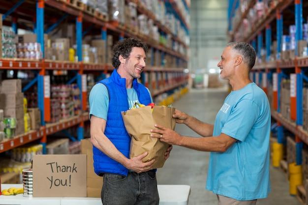 Portret szczęśliwi wolontariuszi trzyma torba na zakupy
