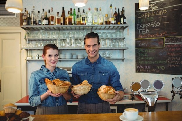 Portret szczęśliwi współpracownicy z chlebami przy kawiarnią