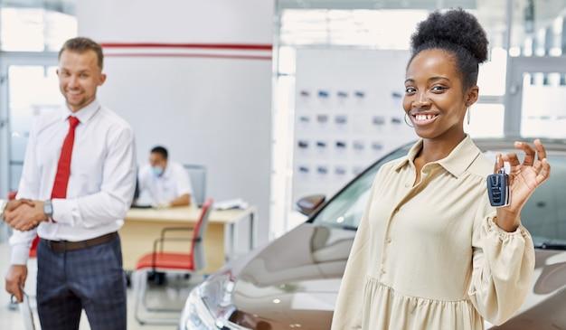 Portret szczęśliwy african american kobieta z kluczyki do samochodu w ręce