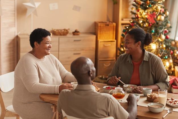 Portret szczęśliwy african-american rodziny siedzi przy stole, delektując się śniadaniem w boże narodzenie rano w domu