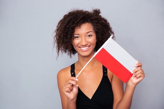 Portret szczęśliwy afro american kobieta trzymając flagę polski na szarej ścianie i patrząc z przodu