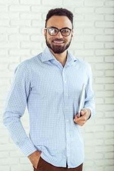 Portret szczęśliwy afroamerican mężczyzna używa laptopu comruter