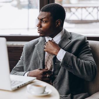 Portret szczęśliwy afrykański biznesmen używa telefon podczas gdy pracujący na laptopie w restauraci.