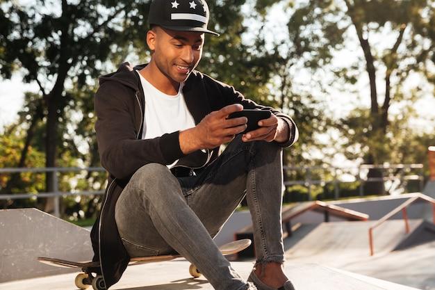 Portret szczęśliwy afrykański facet używa telefon komórkowego
