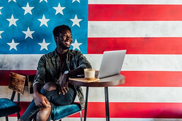 Portret szczęśliwy afrykańskiego biznesmena siedzi w kawiarni i pracuje na laptopie, mieć przerwę na kawę.