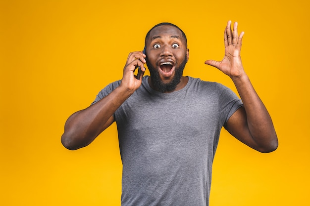 Portret szczęśliwy amerykanina afrykańskiego pochodzenia facet opowiada na telefonie komórkowym.