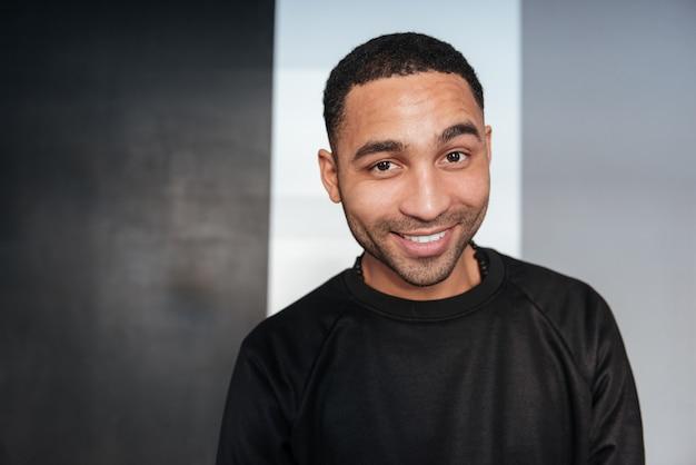 Portret szczęśliwy amerykanina afrykańskiego pochodzenia młody człowiek nad bielem i siwieje ścianę