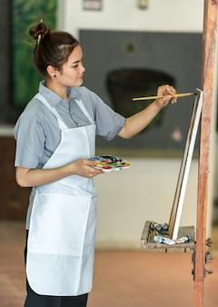 Portret szczęśliwy artysta z paletą w rękach na przedpolu