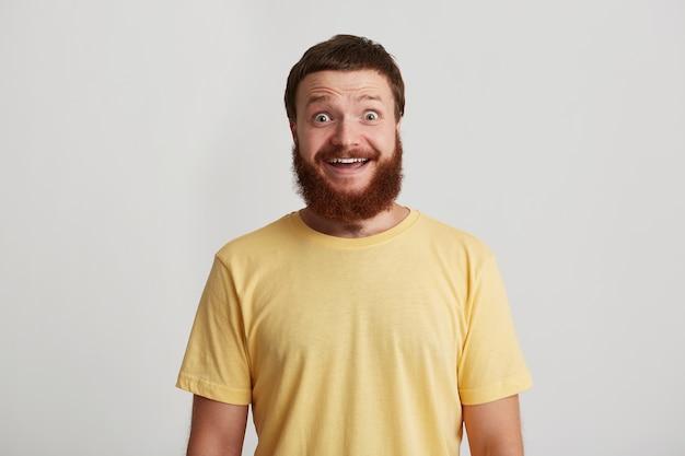 Portret szczęśliwy atrakcyjny młody człowiek hipster z brodą nosi koszulkę wygląda pewnie i szczęśliwie