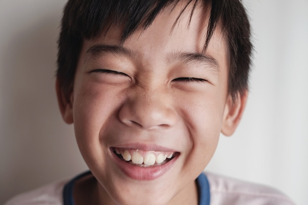 Portret szczęśliwy azjatycki chłopiec preteen śmiejąc się
