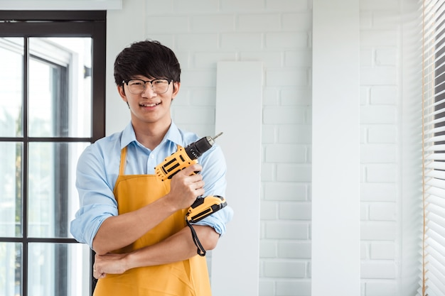 Portret szczęśliwy azjatycki człowiek majsterkowanie montaż mebli czyta instrukcje i dokręca śrubę wiertłem.