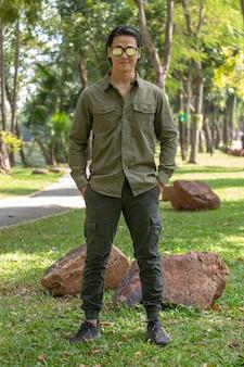 Portret szczęśliwy azjatycki młody człowiek w koszuli z długim rękawem i zielonych spodniach stojący w parku