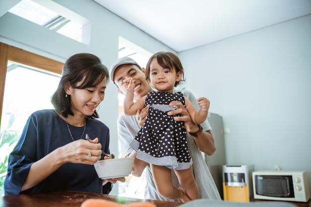 Portret szczęśliwy azjatycki ojciec matki i córki, wspólne gotowanie w nowoczesnej kuchni
