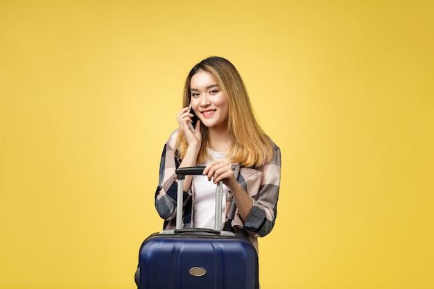 Portret szczęśliwy azjatycki podróżnik z walizką i patrząc na telefon
