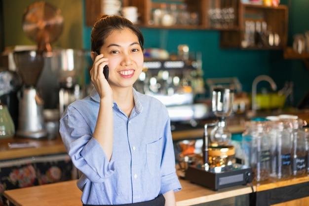 Portret szczęśliwy azjatycki żeński barista bierze rozkaz przez telefonu komórkowego
