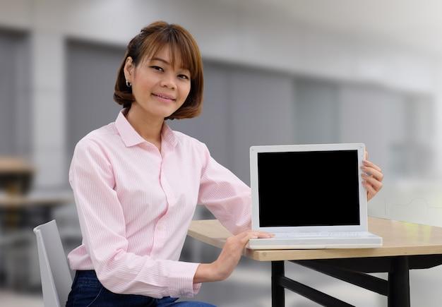 Portret szczęśliwy azjatykci bizneswoman pracuje na laptopu pustym ekranie i zamazujemy