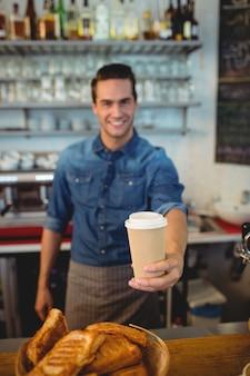 Portret szczęśliwy barista oferuje kawę w rozporządzalnej filiżance przy kawiarnią