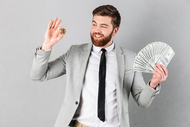 Portret szczęśliwy biznesmen pokazuje bitcoin