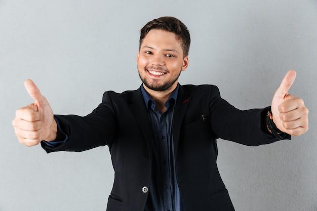 Portret szczęśliwy biznesmen pokazuje dwa aprobaty