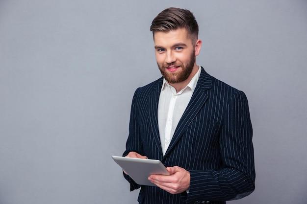 Portret szczęśliwy biznesmen przy użyciu komputera typu tablet na szarej ścianie