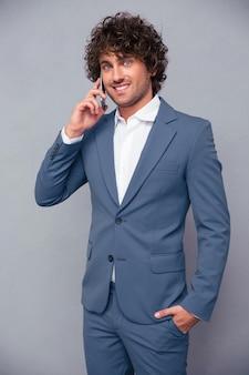 Portret szczęśliwy biznesmen rozmawia przez telefon na szarej ścianie