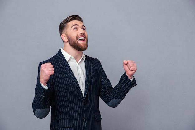 Portret szczęśliwy biznesmen świętuje swój sukces na szarej ścianie