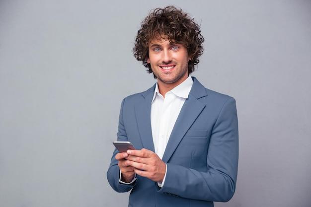 Portret szczęśliwy biznesmen trzymając smartfon i patrząc na kamery na szarej ścianie