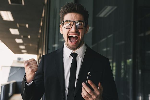 Portret szczęśliwy biznesmen ubrany w oficjalny garnitur, śmiejąc się poza szklanym budynkiem i przy użyciu telefonu komórkowego