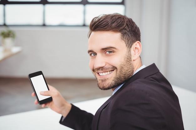 Portret szczęśliwy biznesmen używa telefon komórkowego