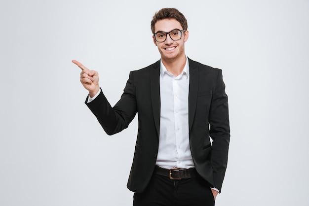 Portret szczęśliwy biznesmen w okularach wskazujący palec daleko nad białą ścianą