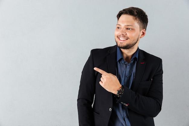 Portret szczęśliwy biznesmen wskazuje palec daleko od