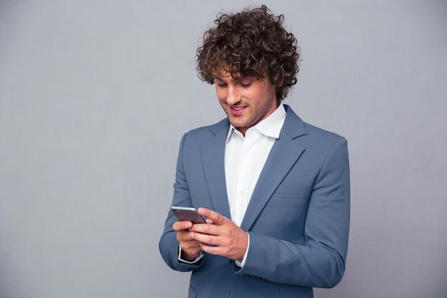 Portret szczęśliwy biznesmen za pomocą smartfona na szarej ścianie