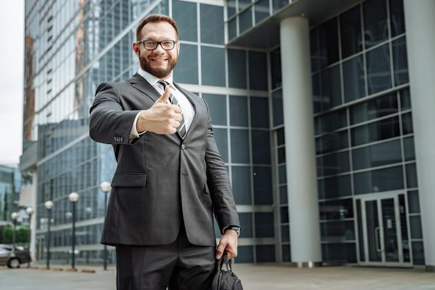 Portret szczęśliwy biznesowy mężczyzna pokazuje jego kciuk up na ulicie