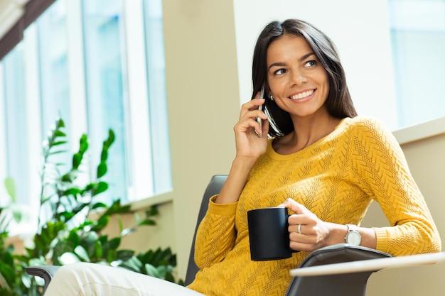 Portret szczęśliwy bizneswoman rozmawia przez telefon i trzymając kubek z kawą w biurze. odwracając wzrok
