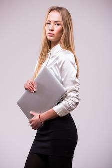 Portret szczęśliwy bizneswoman trzyma laptopa iand patrząc z dala solated nad białą ścianą