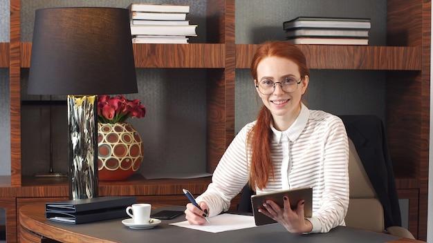 Portret szczęśliwy bizneswoman z pastylka komputerem w pokoju hotelowym.