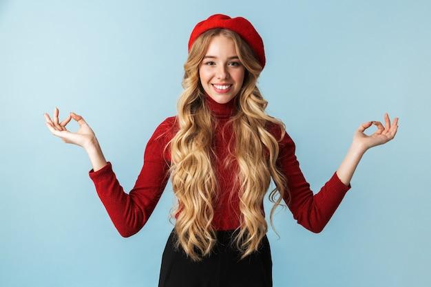 Portret szczęśliwy blond kobieta 20s ubrana w czerwony beret pokazujący zen i gest medytacji stojąc, na białym tle