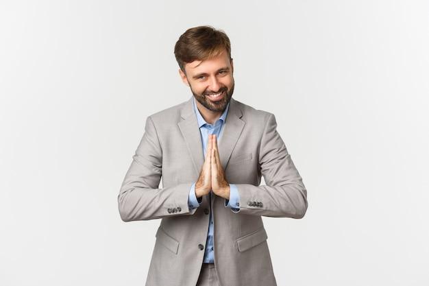 Portret szczęśliwy brodaty biznesmen w szarym garniturze, dziękując za coś