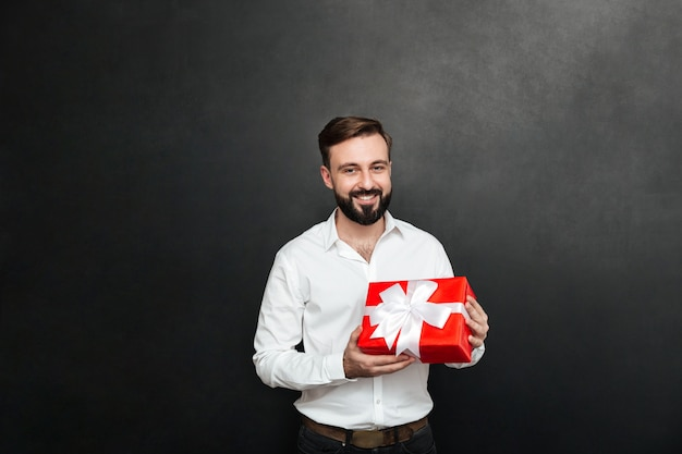 Portret szczęśliwy brodaty mężczyzna trzyma czerwonego prezenta pudełko i patrzeje kamerę nad zmrokiem - szarości ściana