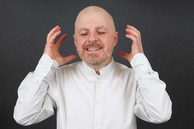 Portret szczęśliwy brodaty mężczyzna w koszuli z podniesionymi rękami