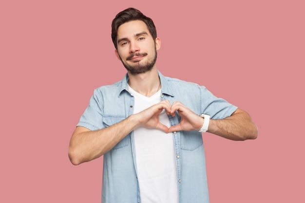 Portret szczęśliwy buźka przystojny brodaty młody człowiek w niebieskiej koszuli stylu casual stojący z gestem ręki miłości na serce i patrząc na kamery uśmiechając się. kryty strzał studio, na białym tle na różowym tle.