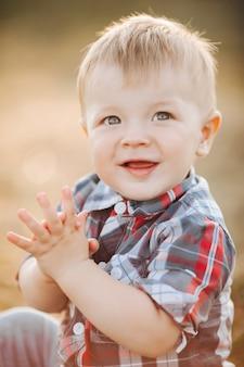 Portret szczęśliwy chłopiec siedzi i klaszcze w dłonie, ciesząc się wakacjami na świeżym powietrzu. koncepcja dzieciństwa